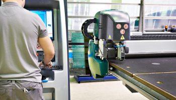Radnik na mašini za sečenje stakla i ogledala